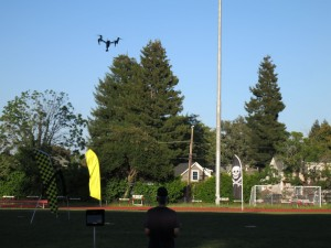 A drone soars at Santa Cruz High School football field, Thursday, as pilots and an enthusiastic audience watched the drones navigate objects during a drone race, an opening event at Drones, Data X Conference. (Photo credit: Karen Kefauver)