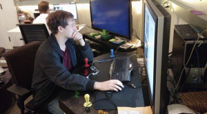Andrew Miller, Lead Designer of A Room Too Far, edits some in-game assets while using his game's arcade cabinet control panel as a desk. Contributed.
