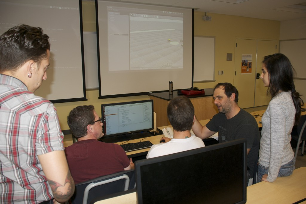 CIS Instructor and Robotics Club Advisor Michael Matera helps students with lines of code to program the Swarmies. (Contributed)