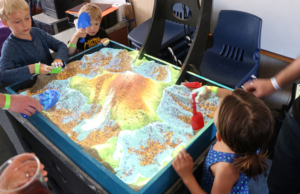 """Fascinated youth dug and mounded in an augmented reality sandbox, which uses a depth sensor that sends infrared light down onto the """"sand"""" material and measures the distance. It sends the information back to a computer, which sends the topography color back down as a feedback loop. Oceans appear at the deepest parts, and snow appears as mountaintops are created."""