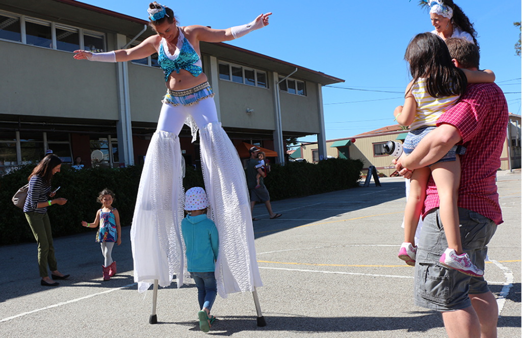 """How do you balance on those, anyway? - Stilt walkers Jamie and Sierra pose with the Clarke family after Jamie used the basketball hoop as a coat hanger to hold her shawl. Later, children were encouraged to walk through their """"legs."""""""
