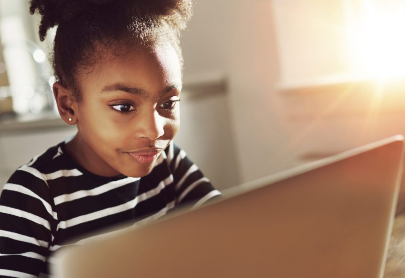 Girls looks attentively at computer screen