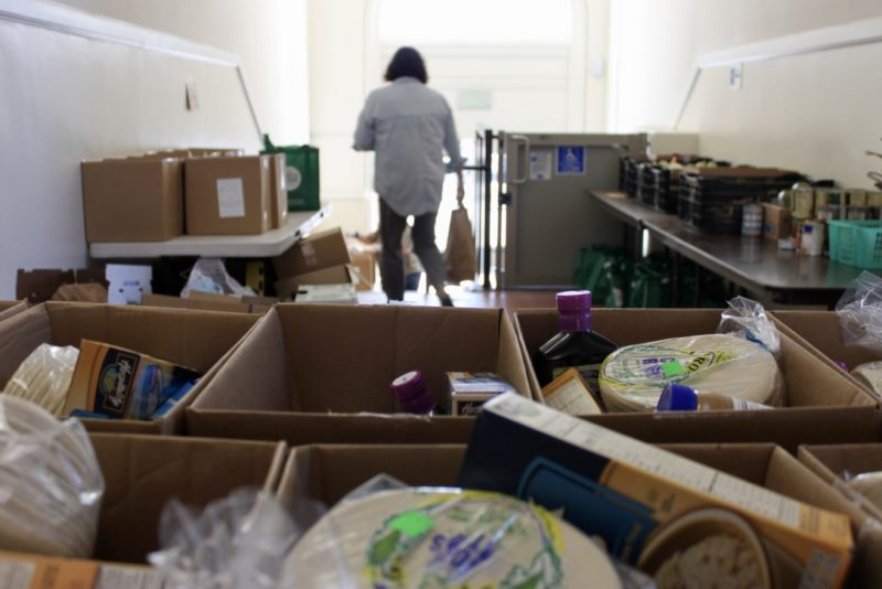 Woman walks out of a room filled with dinated food at Holy Cross church in Santa Cruz County