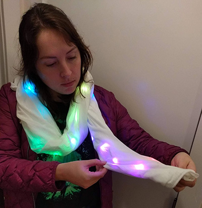 Woman looking at scarf with LED lights